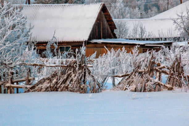 Winter landscape: an old wooden house with a decrepit and rickety fence. stock photo