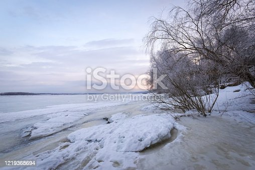 1141614053 istock photo Winter landscape at dawn, riverbank of a frozen ice. 1219368694
