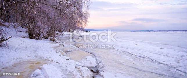 1141614053 istock photo Winter landscape at dawn, riverbank of a frozen ice. 1222731697