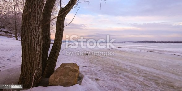 1141614053 istock photo Winter landscape at dawn, riverbank of a frozen ice. 1224495863