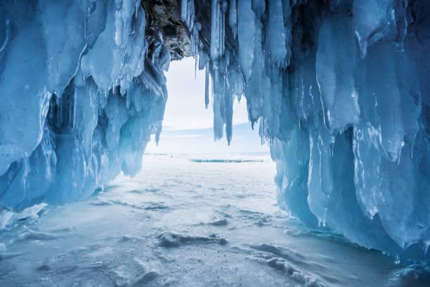 冬の風景、イルクーツク、ロシアのバイカル湖で出口から明るい日差しに冷凍氷の洞窟 - アイスクライミング ストックフォトと画像
