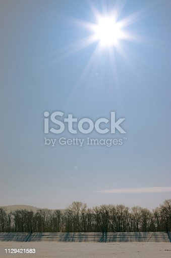 1141614053 istock photo Winter landscape of frozen river and trees. Frost and cold and sunshine 1129421583