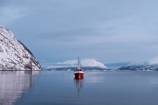 Winter landscape of the fishing boat in the Norwegian fjord.