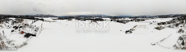 Panoramic photo of winter fields, cottages, snow and mountains against cloudy sky