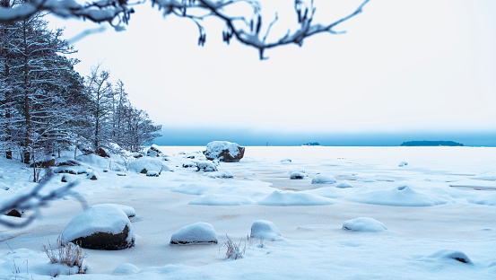 Winter landscape. Snow covered ice on the bay and an island on the horizon.