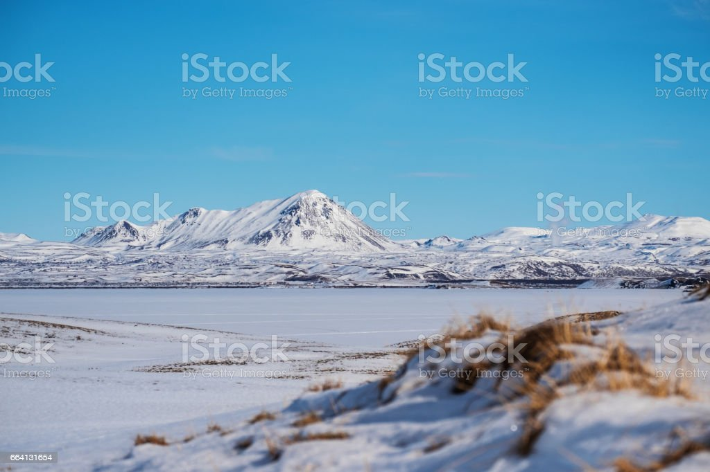 Winter Landscape, sow field with frozen lake and snow mountain with clear blue sky foto stock royalty-free