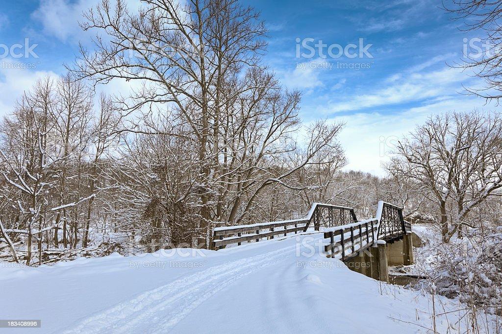 Winter Landscape - Tracks Leading Across Bridge in Fresh Snow stock photo