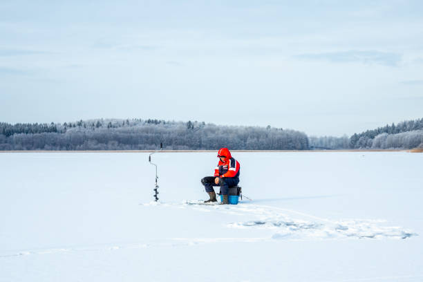 Winter landscape view of one elderly male on a frozen lake ice fishing. stock photo