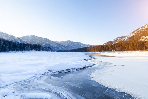 winter landscape with a frozen katun river or a lake in the altai mountains on a sunny day under a blue sky with snowdrifts in a circle divided into warm and cold sides by a stream. - altai nature reserve стоковые фото и изображения