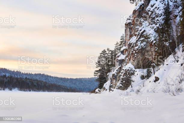 Photo of winter landscape with a wide frozen river in a snowy wooded valley with high cliffs