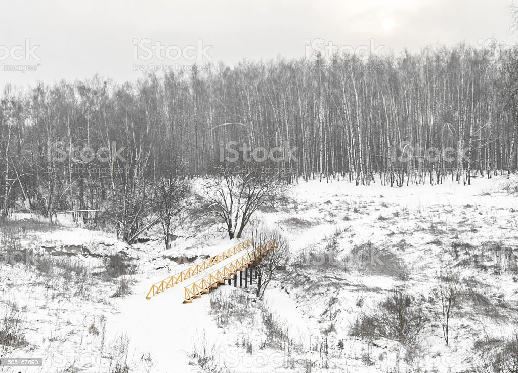 Winter landscape with a yellow wooden bridge stock photo