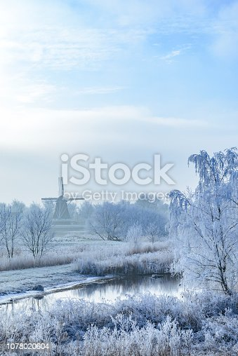 View on an old windmill in the city of Kampen next to the river IJssel in winter in Holland. Kampen is an ancient Hanseatic League in Overijssel, The Netherlands.