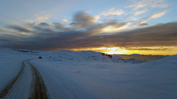 winter landscape with curved road towards cloudy sunset stock photo