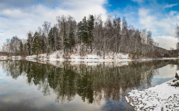 Winter landscape with forest on the lake, clouds in the sky and reflection stock photo