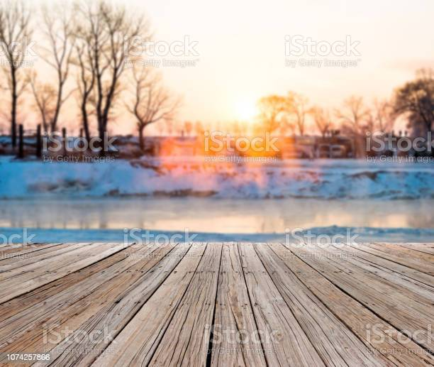 Photo of Winter landscape with frozen lake and people