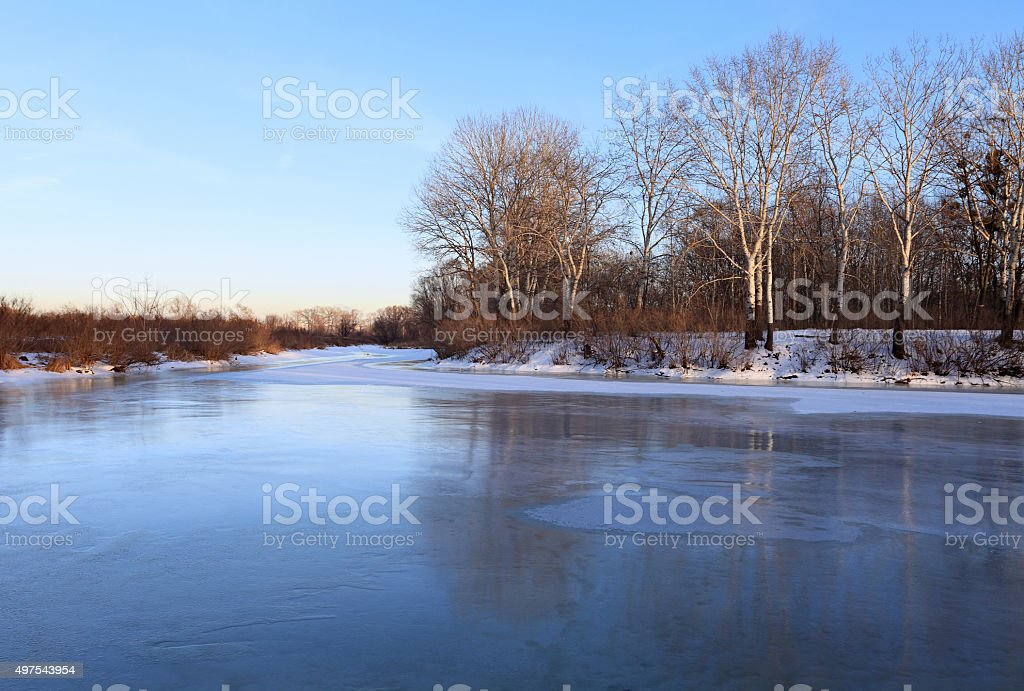 Winter landscape with frozen river and birch trees stock photo