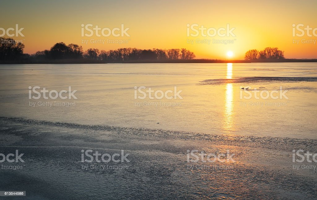 Winter landscape with lake and sunset fiery sky. stock photo
