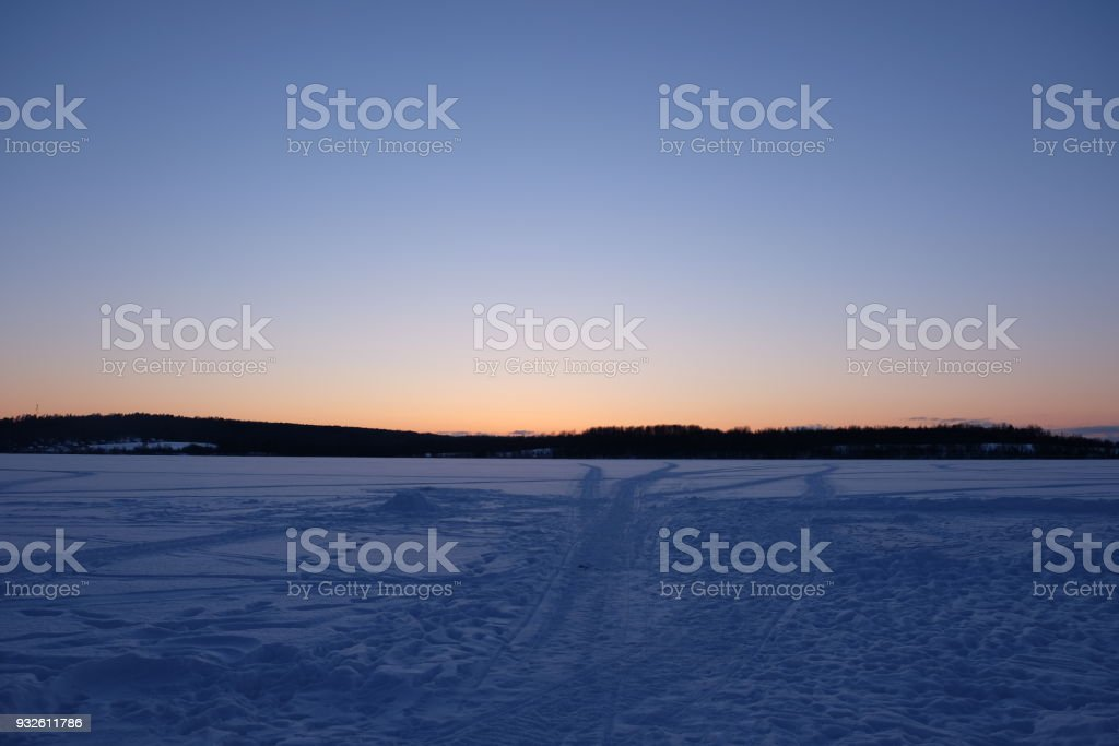 Winter landscape with lake and sunset fiery sky stock photo