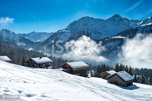 Beautiful winter landscape with ski lodges beside the ski slope and the forest in vorarlberg, austria. There is some fog in the background in front of the mountains of the alps.