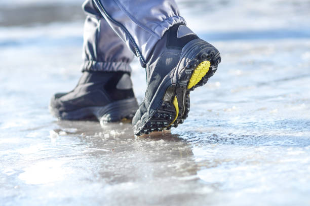 winter legs wearing boots walking on snowy and sleet road - sidewalk stock pictures, royalty-free photos & images