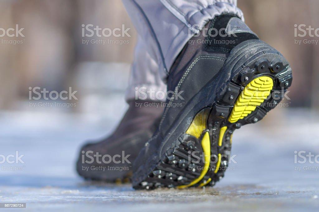 Winter legs wearing boots walking on snowy and sleet road stock photo