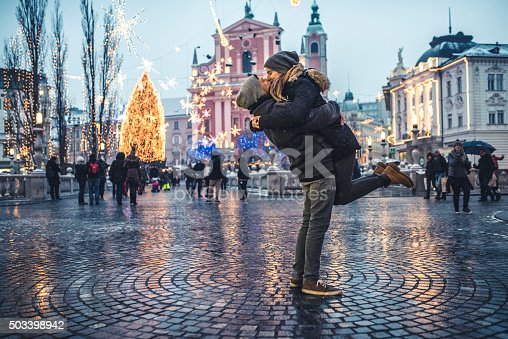 Portrait of young couple in the old city center on cold winter day. Man is holding woman in the air while they are kissing. They are happy together. People and city with christas lights in back, defocused.