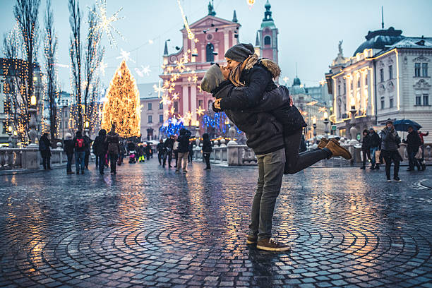 Winter love Portrait of young couple in the old city center on cold winter day. Man is holding woman in the air while they are kissing. They are happy together. People and city with christas lights in back, defocused. ljubljana stock pictures, royalty-free photos & images