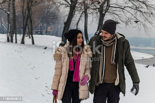 Happy Loving Couple In Snowy Winter Forest, Spending Christmas Vacation Together. Outdoor Seasonal Activities. Lifestyle Capture. Handsome Man Hugging his Beautiful Girlfriend in Park Covered with Snow. Outdoor Seasonal Activities.