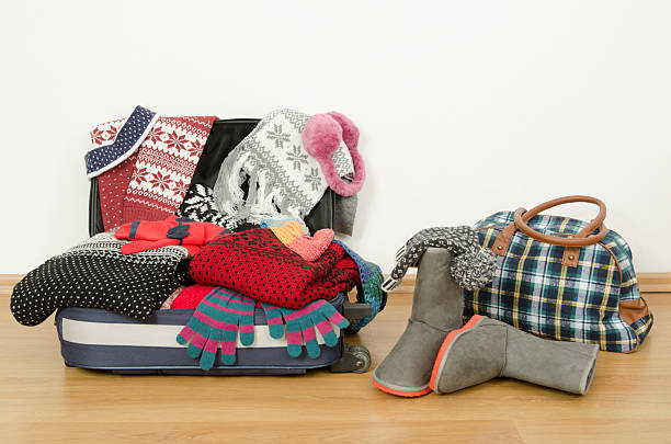 Winter luggage. Suitcase full of wither clothes. stock photo