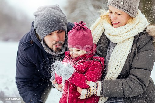 Young happy family playing with snow together outdoors on a beautiful winter day