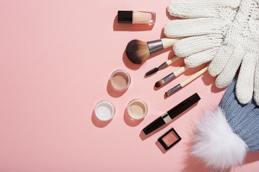 Winter makeup with mittens and bobble hat on pink background