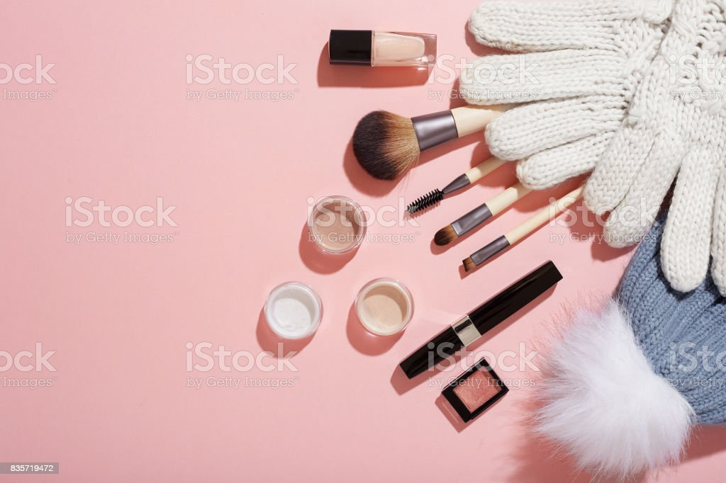Winter makeup with mittens and bobble hat on pink background stock photo