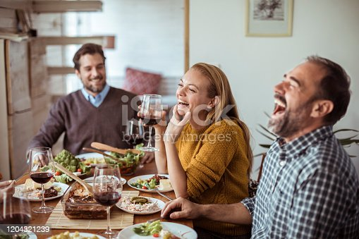 Close up of a group of friends celebrating a winter holiday with a big meal and wine