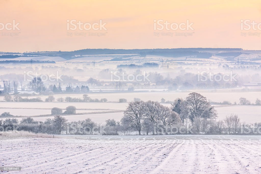 Winter mist over snow-covered fields stock photo
