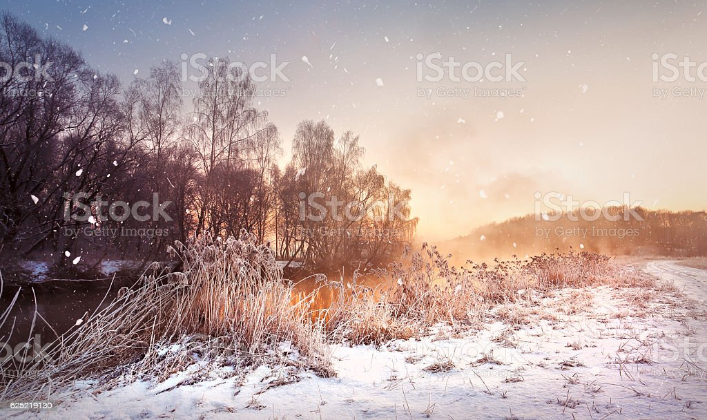 Winter misty dawn on the river. Snowflakes, snowfall. Sunny wint stock photo