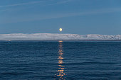 Moonrise over the snowcapped mountains of fjord