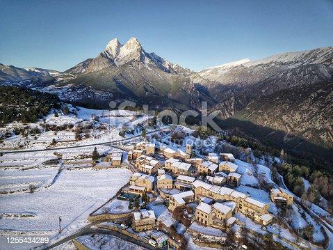 istock Winter morning on the Pedraforca mountain overlooking a snowy town,Catalonia, Spain 1255434289