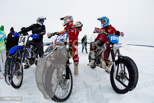 Two men and a woman (#151) line up to start a winter motorcycle ice race on Gull Lake in Alberta, Canada. Their tires have metal studs for traction on the snow and ice. (John Gibson Photo/GibsonPictures)