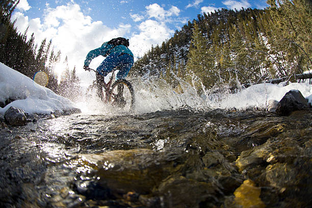 Winter Mountain Bike Creek Crossing A man rides through a creek during a winter mountain bike adventure in the Rocky Mountains of Canada. mountain biking stock pictures, royalty-free photos & images