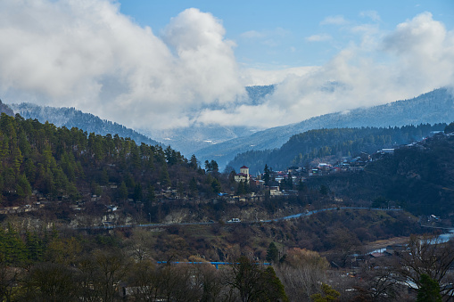 Winter mountain landscape. Small town between mountains. A cloud hangs over the city.