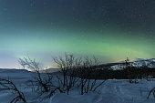Winter night landscape with aurora borealis. Volosnaya Mountain, Kandalaksha, Murmansk region, Russia