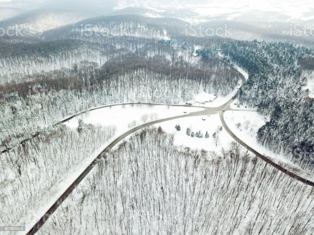 Drone aerial top view of a road going through forest with snow.