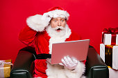 istock Winter noel december eve christmastime package. Aged mature Santa spectacles open mouth eyes white beard isolated red background look pc wondered astonishment face receive unbelievable email letter 1049369624