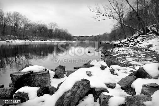 chilly image of snow covered rocks along lake taneycomo in branson, missouri. trout fisherman stands in the water far upstream.