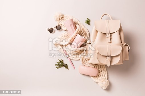 Winter or autumn fashion accessories - christmas gifts. White leather backpack, woollen scarf, pastel pink  mugs, watch and sunglasses. Captured from above (top view, flat lay) on grey background.