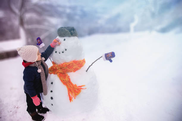 winter-outdoor-aktivitäten für ein kind - schneemann bauen stock-fotos und bilder