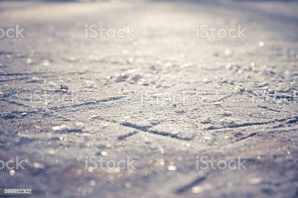 Photo of Winter pattern from snowflakes on shining ice skating rink