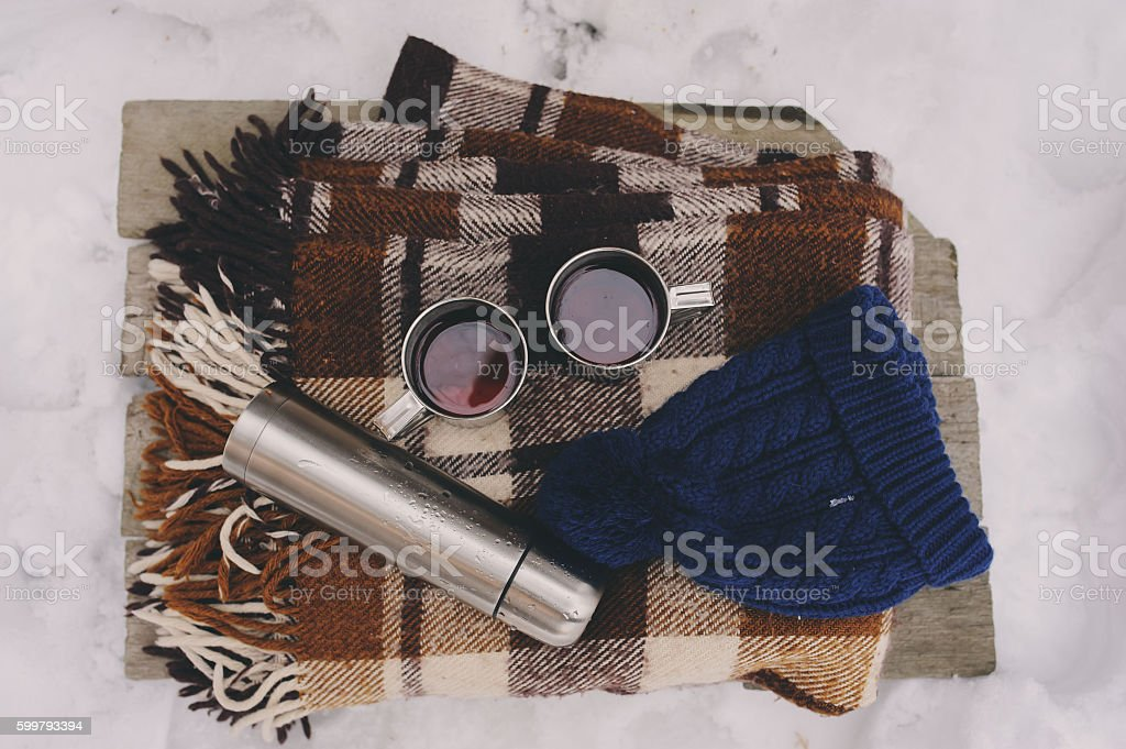 winter picnic on the snow. Hot tea, thermos on blanket. stock photo