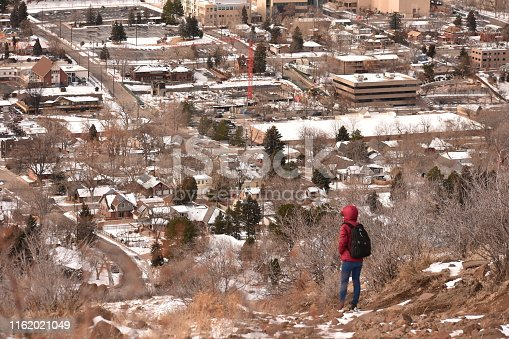 Winter picture - Backpacker looking towards Golden city, Colorado, from the top of the red rock platform.