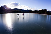 Two women enjoy a winter skate on an outdoor pond in the Rocky Mountains of Canada. They are both carrying hockey sticks and are accompanied by their pet dog.